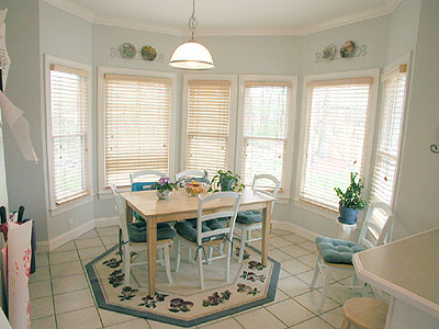 just off the kitchen is the laundry room with ceramic tile flooring wire shelving two windows to the front with 2 wood blinds and plenty of room for breakfast area lighting